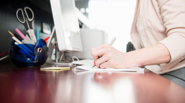 Woman writing at reception desk