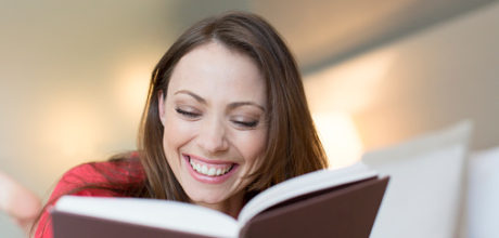 Smiling woman reading book in bedroom