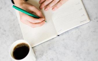 Woman writing on diary, coffee on side