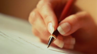 Hand signing document with pen, close-up